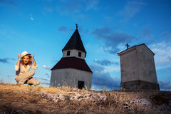 Young woman posing by the church on the hill. Young positive woman posing by the church on the hill. Magical evening place Stock Photo