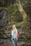 Young woman posing in dark forest. Young woman tourist posing in dark forest royalty free stock photography