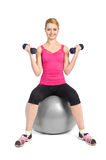 Young woman posing with dumbbells. Sitting on fitness ball, on white background Royalty Free Stock Images