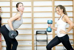 Young woman posing exercise with bar and dumbbell in gym Royalty Free Stock Photos