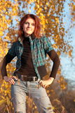 Young woman posing in the fall. Young woman with red hair posing against bright autumn leaves Stock Photo