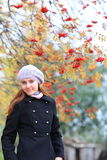 Young woman posing in the fall. Young woman with red hair posing against bright autumn leaves Royalty Free Stock Images