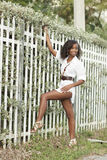 Young woman posing by a fence Royalty Free Stock Images