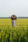 Young woman posing in a field summer photo. Girl in a striped dress and hat. A slender woman Royalty Free Stock Image