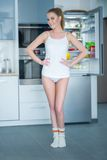 Young woman posing in front of an open fridge. Slender young woman posing in her sleepwear in front of an open fridge with her hands on her hips as she shows off royalty free stock photography