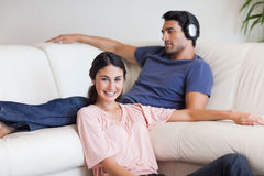 Young woman posing while her husband is listening to music Stock Images