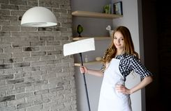 A young woman posing while holding a mop cleaner Royalty Free Stock Image