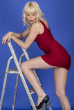 Young Woman Posing Ladder with Short Red Dress Revealing Her Long Legs Stock Photo