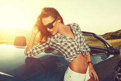 Young woman posing leaning on convertible car at suns. Attractive young woman posing leaning on convertible car at sunset Stock Photo