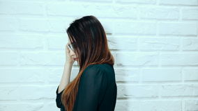 A young woman posing, looking at the camera on a white brick wall background. stock video footage