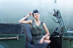 A young woman posing in military clothes in a car Stock Images