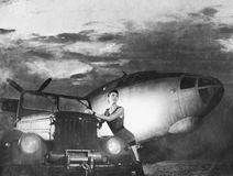 A young woman posing near a car and a plane Royalty Free Stock Images