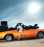 A young woman posing near an orange retro car Stock Image