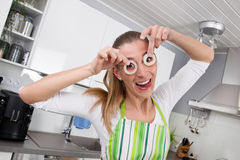 Young woman posing with onion rings in the kitchen Stock Photography
