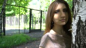 Young woman posing in a park near birch tree. Slow mo, stedicam shot stock footage