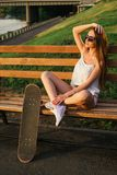 Young woman posing at the park with skateboard Royalty Free Stock Photography
