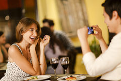 Young woman posing for a photo. Beautiful young women posing for a smartphone photo in a restaurant Royalty Free Stock Photography