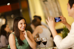 Young woman posing for a photo. Beautiful young women posing for a smartphone photo in a restaurant Royalty Free Stock Photos