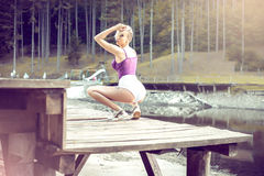 Young woman posing on pier wearing white shorts. Stock Images