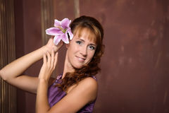 Young woman posing with a pink lily Stock Images