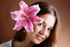 Young woman posing with a pink lily Royalty Free Stock Image