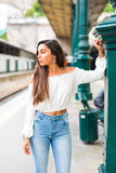 Young woman posing at platform on train station. Waiting a train or metro Stock Images