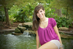 Young woman posing in a pond. Young woman posing next to a pond in a beautiful park of Houston Royalty Free Stock Photography