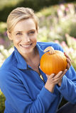 Young woman posing with pumpkin in garden. Smiling royalty free stock image