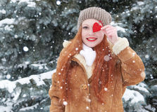 Young woman posing with red heart toy. Winter season. Outdoor portrait in park. Snowy weather. Valentine concept. Stock Photo