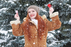 Young woman posing with red heart toy. Winter season. Outdoor portrait in park. Snowy weather. Valentine concept. Royalty Free Stock Photography