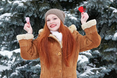 Young woman posing with red heart toy. Winter season. Outdoor portrait in park. Snowy weather. Valentine concept. Royalty Free Stock Image
