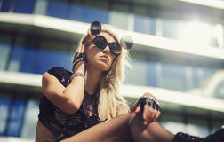 Young woman posing in round glasses. On a background of a modern building stock photography