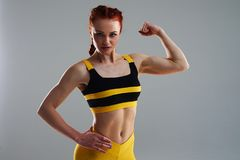 Young woman posing and showing biceps. In studio Royalty Free Stock Photos