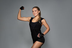 Young woman posing and showing muscles in gym. Sport, fitness and people concept - young woman posing and showing muscles in gym stock images