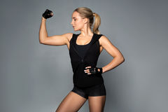 Young woman posing and showing muscles. Sport, fitness and people concept - young woman posing and showing muscles in gym stock images