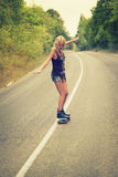 Young woman posing with a skateboard Royalty Free Stock Image