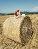 Young woman posing with the stack of straw and enjoying the suns Stock Photography