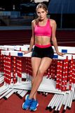 Young woman posing on stadium. Beautiful woman in sports clothes and shoes posing at the camera Stock Photos