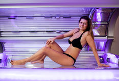 Young woman posing on tanning bed. Indoors solarium shot Stock Image
