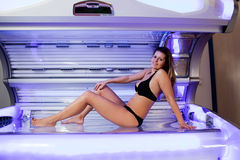Young woman posing on tanning bed Stock Images
