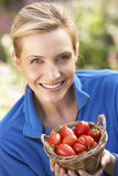 Young woman posing with tomatoes in garden Stock Photo