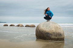 Young woman posing on top of one Moeraki Boulder, New Zealand Stock Photo