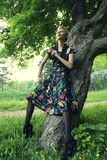 Young woman posing on a tree Royalty Free Stock Image