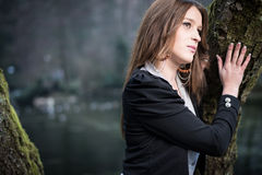 Young woman posing at the tree. Young woman in jacket posing at the tree Royalty Free Stock Photography
