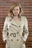 Young woman posing in a trenchcoat. Beautiful young woman is posing in a trenchcoat Royalty Free Stock Images
