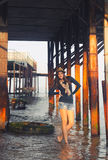 Young woman posing under the pier. Royalty Free Stock Photos