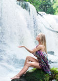 A young woman posing on a waterfall background Royalty Free Stock Image