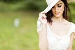 Young woman posing in a white dress with a hat Stock Photo