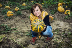 Young woman posing with yellow pumpkin in the field Royalty Free Stock Photos