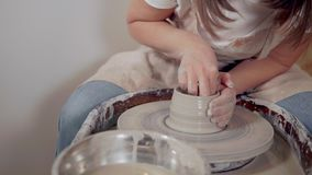 Female ceramist is shaping clay cup on potter`s wheel in workshop. Young woman potter is making clay tableware in studio. She is using a potter`s wheel for stock video footage
